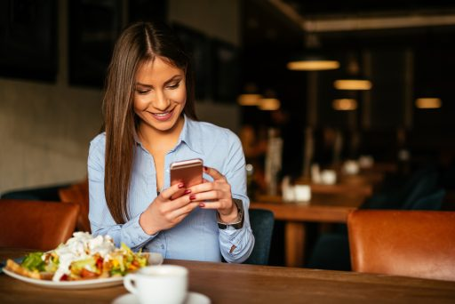Beautiful woman having breakfast and texting on a mobile phone.